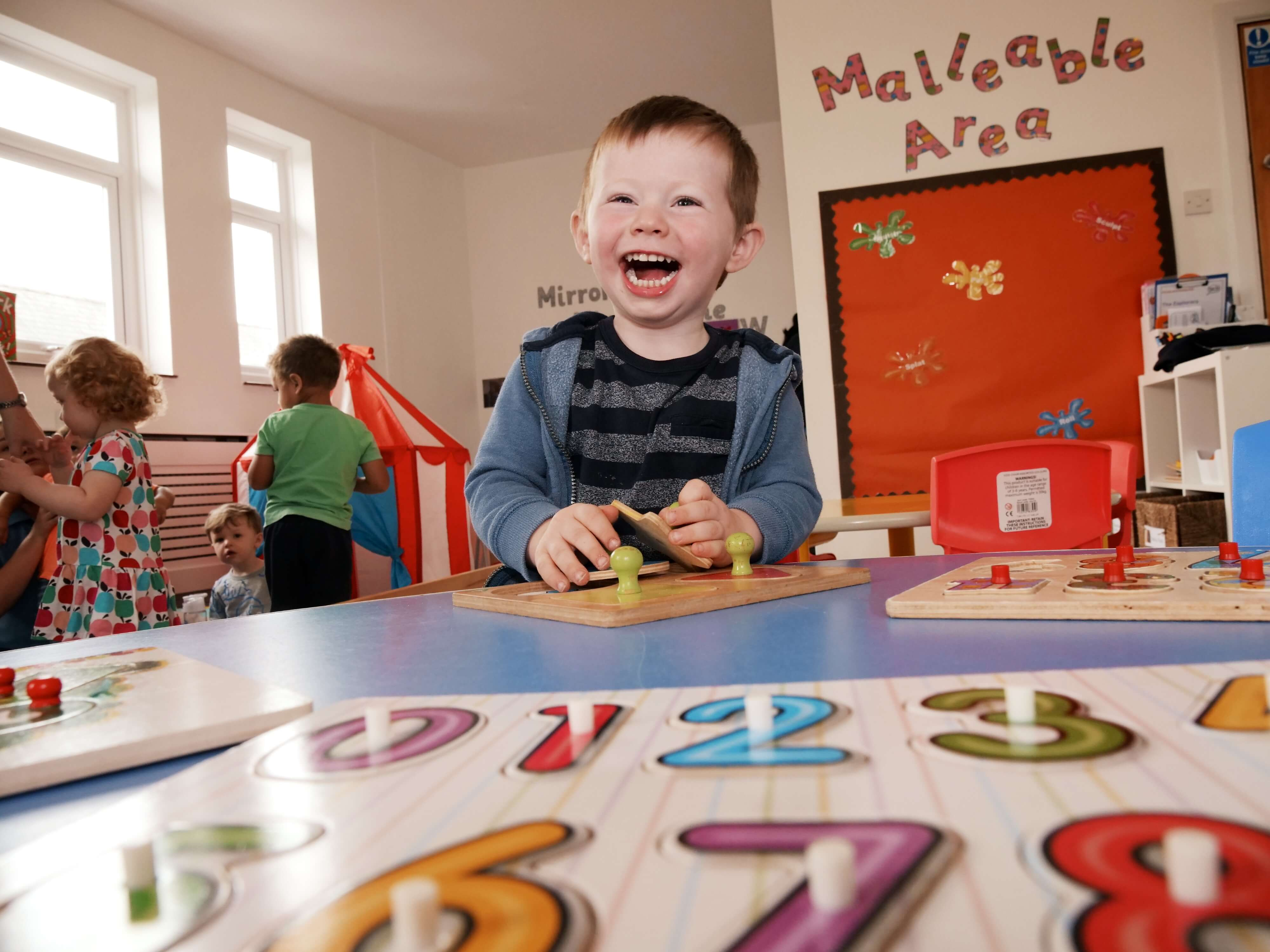 a happy boy laughing at nursery