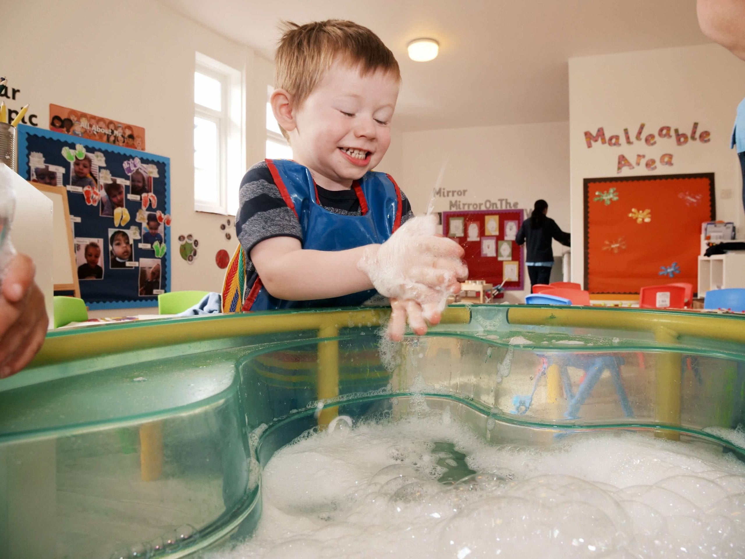 image of boy playing happily at nursery