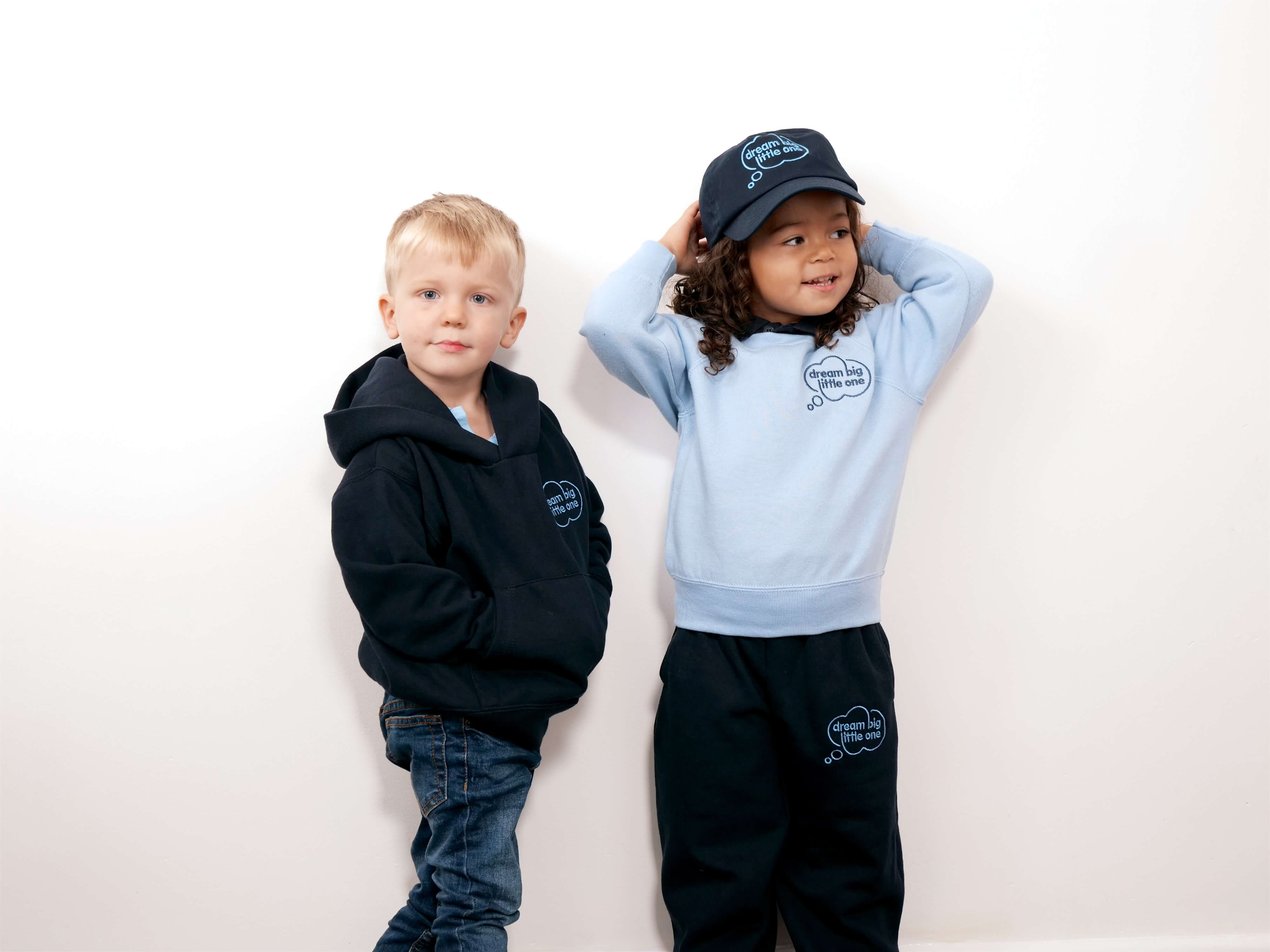 Image of two children wearing a Dream Big Little One day nursery shirt