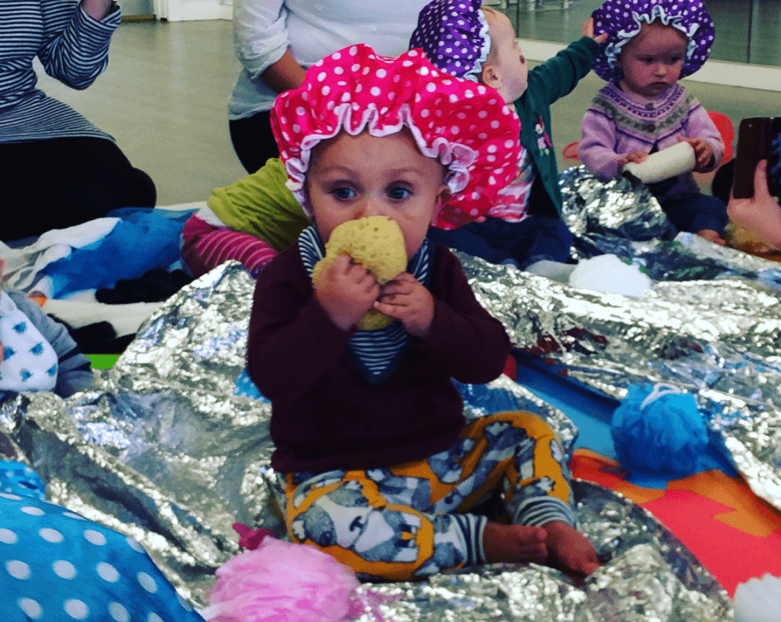 A little girl in a shower cap having fun at baby classes at Dream Big Little one day nursery